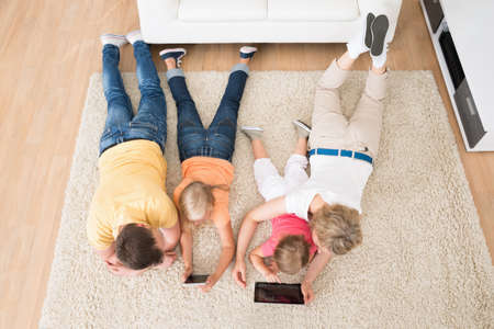 Kids Using Tablets Lying On Carpet At Home photo