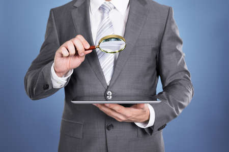 magnifying glass man: Auditor holding magnifying glass and tablet. Over blue background