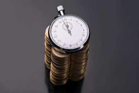 Stopwatch on stack of euro coins over black background