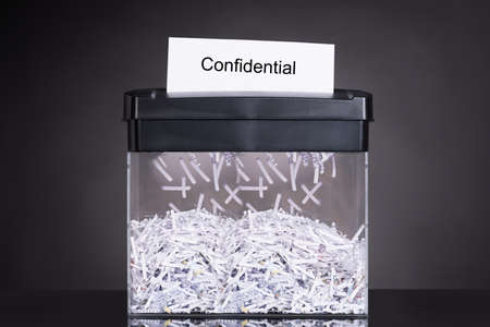 Shredded destroying confidential document over black background Standard-Bild