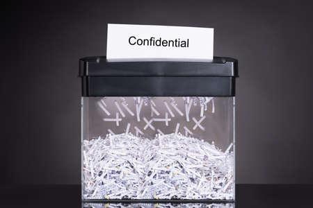 Shredded destroying confidential document over black background Archivio Fotografico