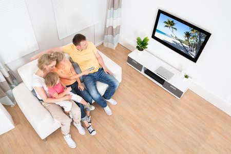 Familia joven que ve la TV junto en el país