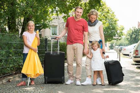 Familia feliz joven que viaja ir de vacaciones. Disparo al aire libre