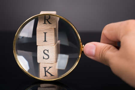 risk management: Inspecting risk blocks with loupe over black background Stock Photo