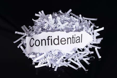 paper shredder: Shredded paper in data confidentiality concept over black background
