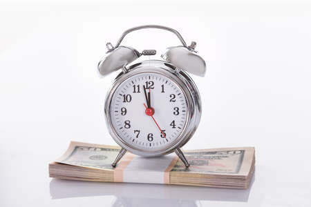 Alarm Clock on US Dollars. Isolated on white photo