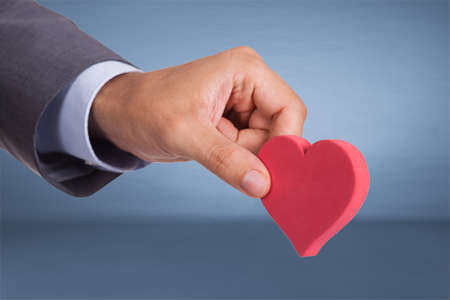 hand over: Hand holding heart shape over blue background Stock Photo