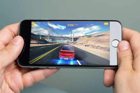 Berlin; Germany - October 10; 2014: Cropped image of hands\ playing Asphalt 8 game on Apple iPhone 6. Asphalt8: Airborne is\ 2013 racing video game; developed and published by Gameloft; it was\ released on August 22; 2013\