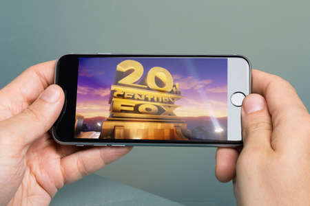 twentieth: Berlin; Germany - October 10; 2014: Cropped image of hands holding Apple iPhone6 with logo of Twentieth Century Fox Film Corporation. Twentieth Century-Fox Film Corporation is one of the six major American film studios and was formed on May 31; 1935