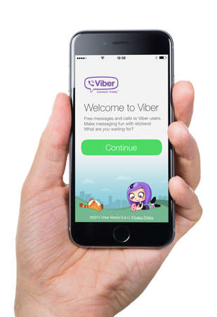 Berlin; Germany - October 10; 2014: Cropped image of hand holding Apple iPhone 6 with Viber welcome page on screen against white background. Viber is famous instant messaging application for smartphones