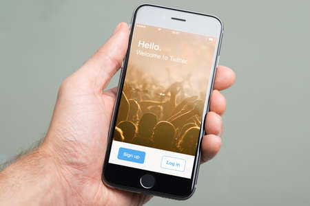microblogging: Berlin; Germany - October 10; 2014: Cropped image of hand holding an Apple iPhone6 with the home screen of social media website Twitter. Twitter is a social media online service for microblogging and networking communication
