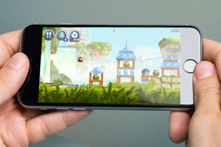play popular: Berlin; Germany - October 10; 2014: Cropped image of hands playing Angry Birds Star Wars game on Apple iPhone6. Angry Birds game was developed by Finnish company Rovio Entertainment first released in 2009
