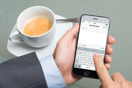 Berlin; Germany - October 10; 2014: Cropped image of businessman text messaging on Apple iPhone 6 at table. Apple iPhone6 was launched on September 19; 2014