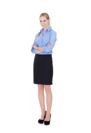 Full length portrait of happy young businesswoman standing arms crossed over white background photo