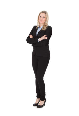Full length portrait of confident young businesswoman standing arms crossed over white background photo