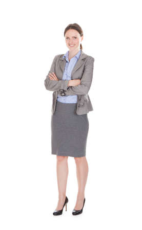 Full length portrait of smiling businesswoman with arms crossed standing against white background photo