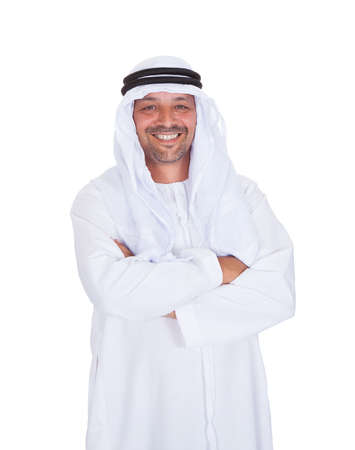 arabic man: Portrait of smiling Arabian man standing arms crossed over white background Stock Photo