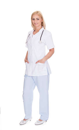 Full length portrait of female doctor standing isolated over white background Stock Photo