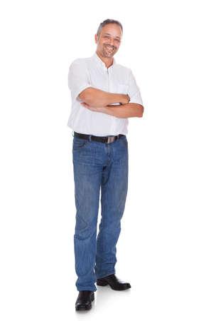 mani incrociate: Ritratto di lunghezza di sorridente maturo uomo in piedi braccia incrociate su sfondo bianco