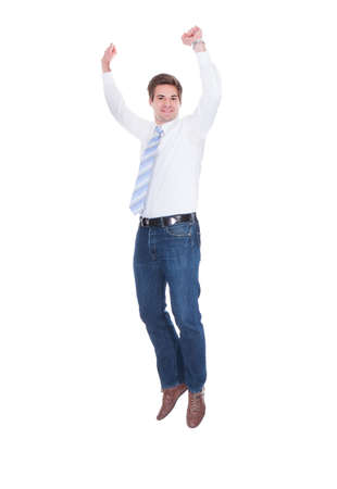 Full length portrait of young businessman jumping with arms raised over white background photo