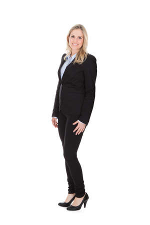 Full length portrait of confident young businesswoman standing over white background photo