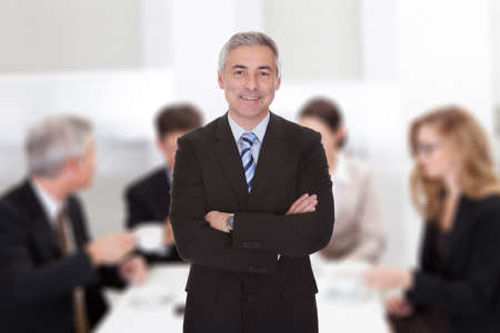 Portrait of confident senior businessman standing arms crossed against colleagues in meeting room
