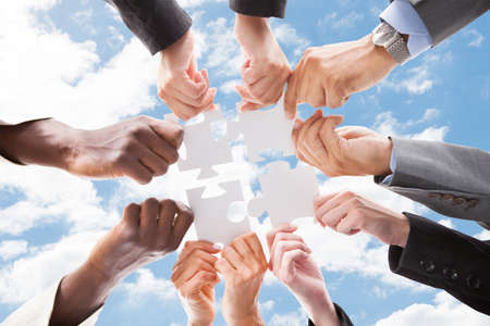 team work: Directly below shot of multiethnic business people assembling jigsaw puzzle against sky