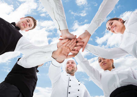 Directly below shot of chef and waiters piling hands against sky