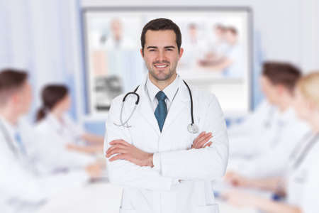 Portrait of young doctor with arms crossed against team video conferencing in meeting room