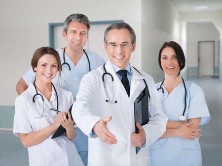 gente saludando: Retrato de feliz médico senior que ofrece apretón de manos mientras está de pie con el equipo en el hospital
