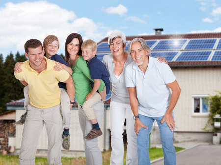 paneles solares: Retrato de familia feliz de múltiples generaciones de pie contra el hogar