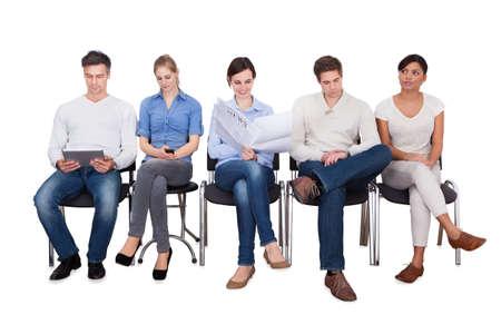 Volledige lengte van ondernemers doen van verschillende activiteiten, terwijl zitten op stoelen tegen een witte achtergrond
