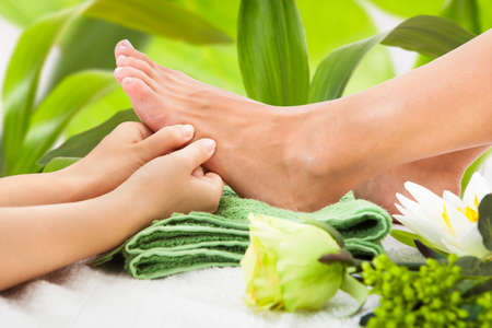 relax massage: Cropped image of masseuse massaging womans foot against leaves at spa Stock Photo