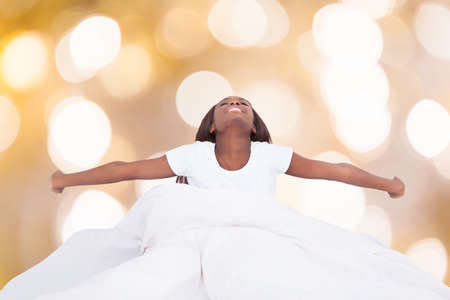 arm outstretched: Happy young african woman stretching in bed