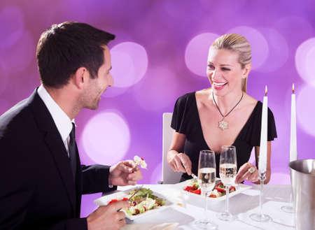 luz de velas: Feliz pareja de jóvenes disfrutando de cena con velas en la mesa de restaurante Foto de archivo
