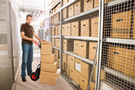 storeroom: Portrait of delivery man with stacked cardboard boxes on hand truck at warehouse