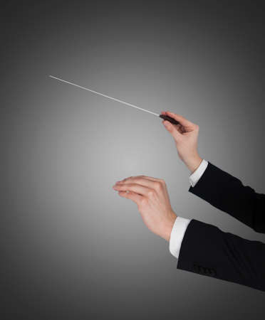 choral: Closeup of music conductors hands holding baton against gray background