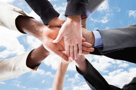 la union hace la fuerza: Detalle de las manos de la gente de negocios multi�tnica en la parte superior de la otra unidad que simboliza contra el cielo