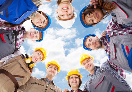 Directly below portrait of multiethnic architects standing in huddle against sky Stock Photo