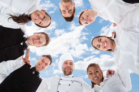 Directly below portrait of happy chef and waiters standing in huddle against sky
