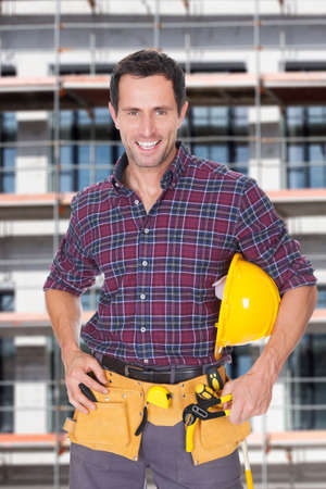 architect tools: Portrait of happy architect with hardhat and tools against building