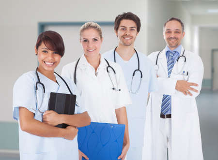 Portrait of multiethnic doctors with stethoscopes around neck standing in hospital photo