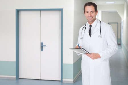Portrait of happy confident doctor holding file in hospital corridor photo