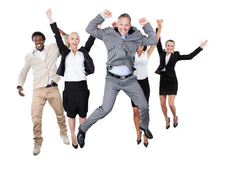 razas de personas: Retrato de equipo de negocios exitoso con los brazos levantados de pie sobre fondo blanco