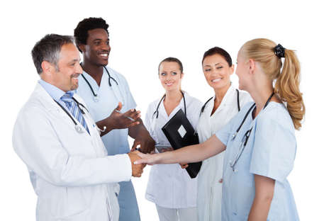 Male and female doctors making handshake while colleagues looking at them over white background photo