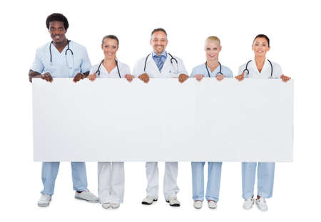 Full length portrait of confident medical team holding blank billboard over white background Stock Photo