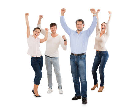 Full length portrait of successful businesspeople with arms raised standing against white background photo