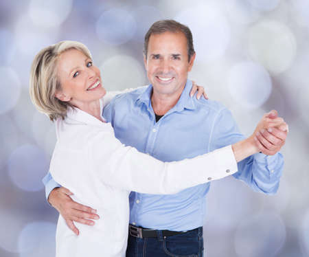 woman dancing: Portrait of affectionate couple dancing against colored background Stock Photo