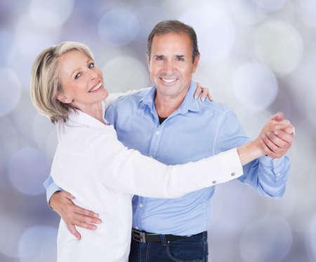 Portret van aanhankelijk paar dansen tegen gekleurde achtergrond