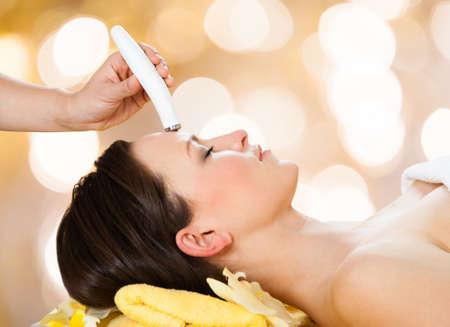 beauty wellness: Jonge vrouw die microdermabrasie behandeling op het voorhoofd bij beauty spa